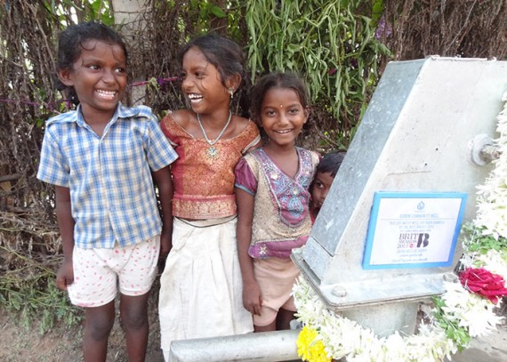 Four smiling children at the Gudem community well