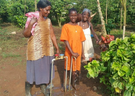 Mrs Sekindi with her daughters at their tap stand at their home in Wajinja village edit
