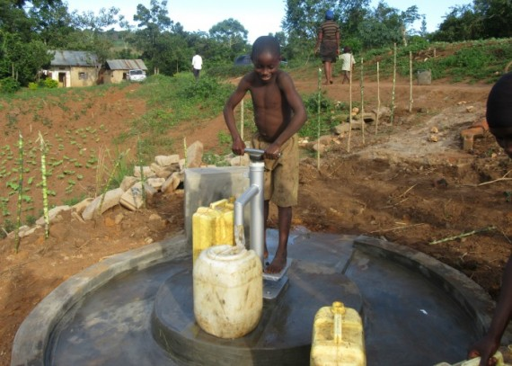 A child pumping water at their water source
