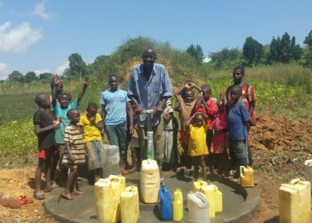 resized Kaweesi Andrew with some children at their new well